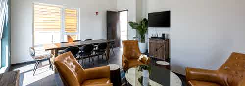 Interior daytime view of boater's lounge with big screen TV, conference table and armchairs at AMLI Marina Del Rey apartments