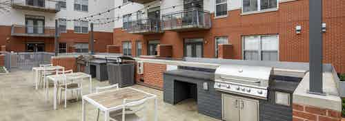 Grill area at AMLI Downtown apartments with two steel grills set in dark gray brick and white seating and hanging lights above