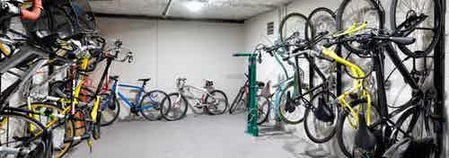 Resident bicycle storage room with bike repair station and bikes hanging on two walls at AMLI River Oaks apartment building
