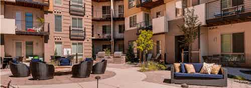 A daytime view of a courtyard at AMLI Cherry Creek apartments with a fire pit with surrounding trees and chairs and couches