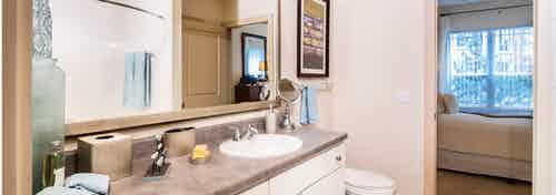 A bathroom at AMLI Park Avenue apartments with a large mirror and a granite counter top with sink and peek into the bedroom