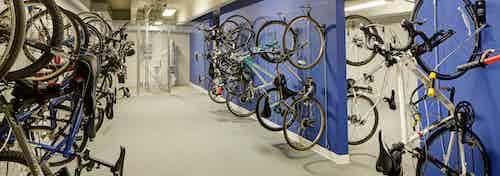Interior view of bike storage room at AMLI Deerfield apartment community with blue walls and several vertical bike racks