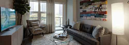Living room at AMLI Lofts with grey and white furnishings paired with colorful wall art and a glass door leading to a balcony