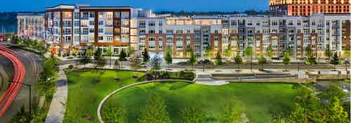 Exterior of AMLI Buckhead apartment community at night with light coming through the windows and trees lining the sidewalk
