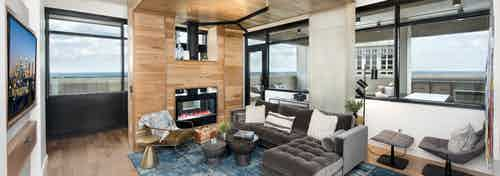 Private room within AMLI Lenox clubhouse seating area and fireplace set in wood wall with floating ceiling and a television