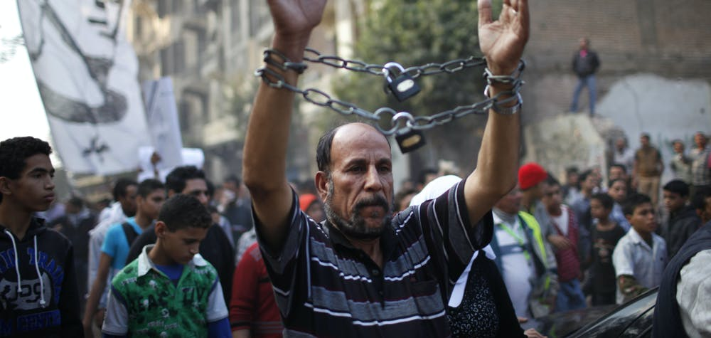 A mourner wearing chains attends the funeral of youth activist Gaber Salah, also known as Gika, at Tahrir in Cairo November 26, 2012. State news agency MENA reported that Salah, a member of the 6th of April youth movement, was wounded with birdshot in the head, neck, chest and arms and put on life support in intensive care, following last Monday's clashes between police and protesters on the anniversary of lethal street violence between activists and security.