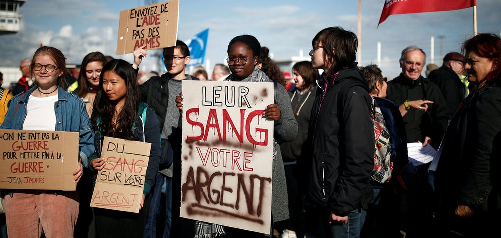 """People attend a demonstration to protest against the loading of weapons aboard the Bahri-Yanbu, a cargo ship operating for Saudi Arabia's defence and interior ministries, in Le Havre, France, May 9, 2019. The banner reads: """"Their blood, your money""""."""