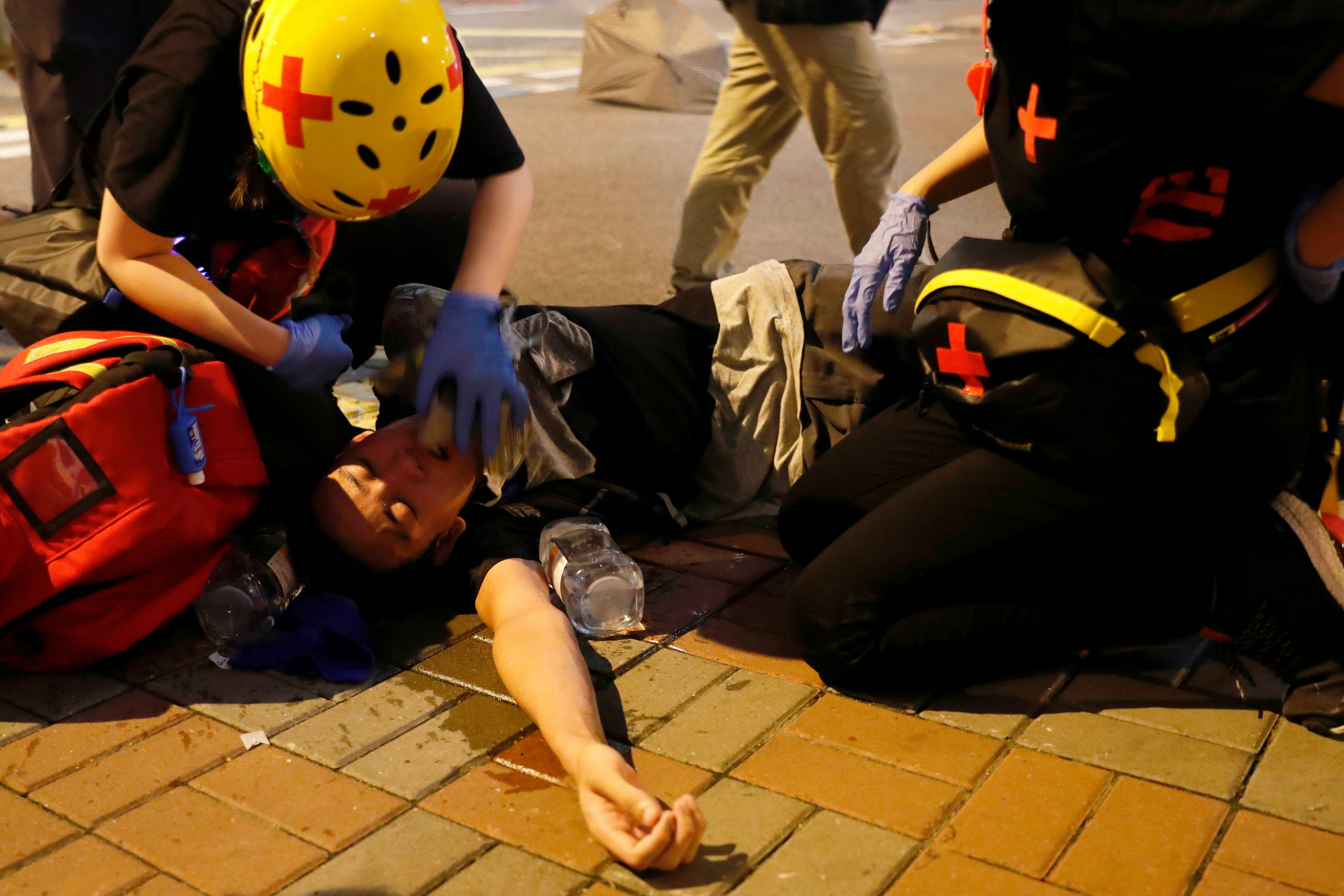 An anti-extradition bill demonstrator receives medical attention after riot police fire tear gas after a march to call for democratic reforms, in Hong Kong