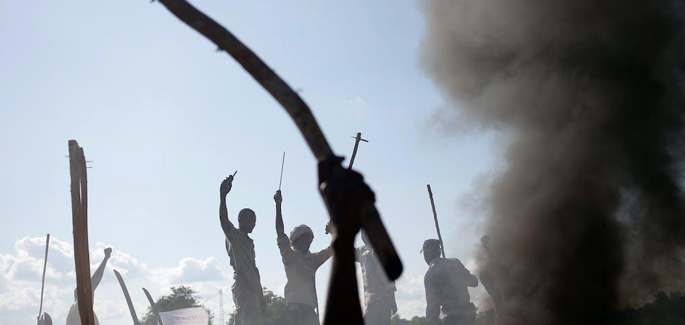 Des hommes font un geste devant une barricade brûlée lors d'une manifestation contre les soldats français à Bambari