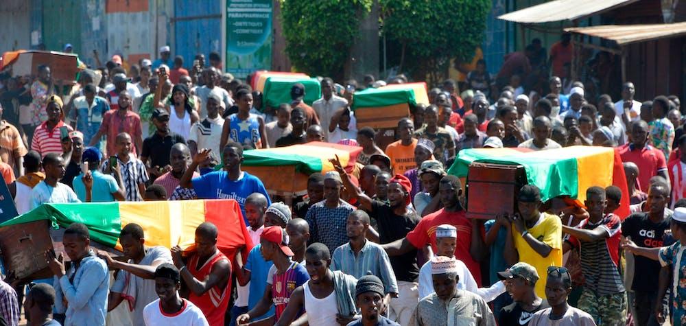 Des manifestants fuient alors que la police lance des pierres et du gaz lacrymogène à Wanindara, un bastion de l'opposition situé dans la banlieue nord de Conakry (27 février 2020).
