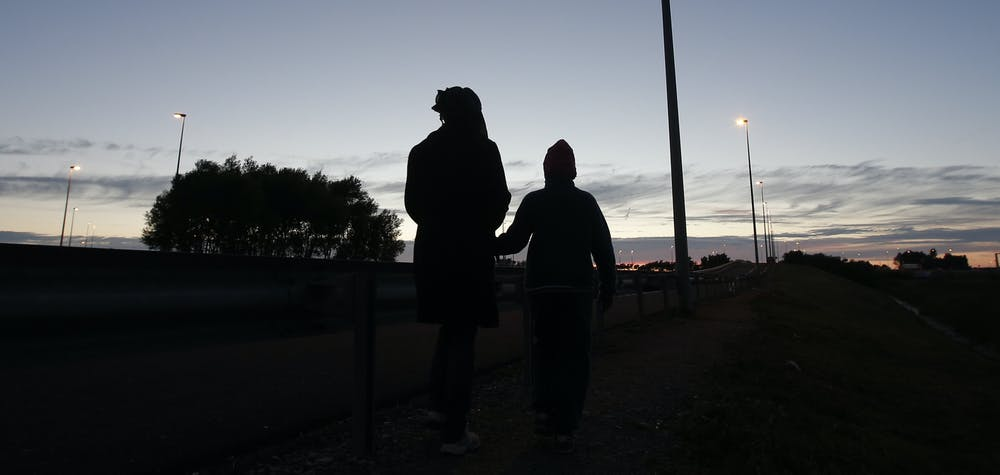 """An Eritrean mother and her daughter are seen in silhouette as they walk along the motorway near the Channel Tunnel entrance near Calais, France, August 6, 2015. For most of the 3,000 inhabitants of the """"Jungle"""", a shanty town on the sand dunes of France's north coast, the climax of each day is the nightly bid to sneak into the undersea tunnel they hope will lead to new life in Britain."""