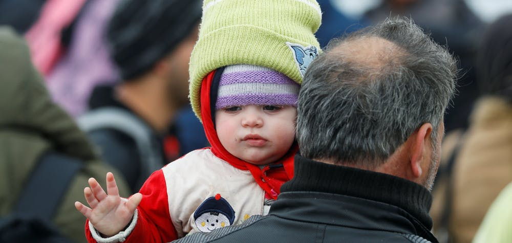 A migrant holding a child walks near the Turkey's Pazarkule border crossing with Greece's Kastanies, near Edirne, Turkey, March 4, 2020.