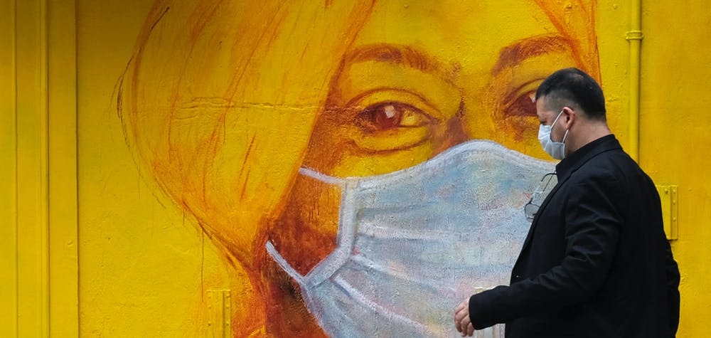 A man with protective mask walks on the street, following the novel coronavirus disease (COVID-19) outbreak, in Hong Kong, China March 27, 2020. REUTERS/Tyrone Siu