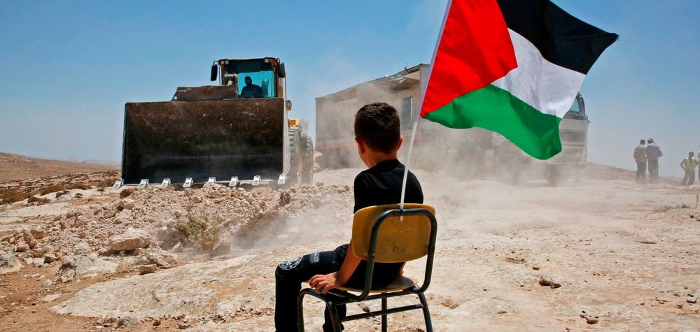 A Palestinian boy sits on a chair with a national flag as Israeli authorities demolish a school site in the village of Yatta, south of the West Bank city of Hebron and to be relocated in another area, on July 11 2018. (Photo by HAZEM BADER / AFP) (Photo credit should read