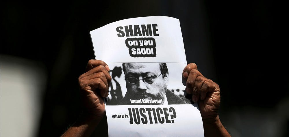 A member of Sri Lankan web journalist association holds a placard during a protest condemning the murder of slain journalist Jamal Khashoggi in front of the Saudi Embassy in Colombo