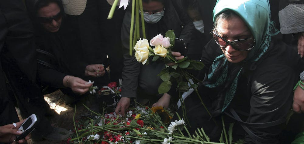 Iranians put flowers onto the grave of Neda Agha-Soltan as mourners gather at Tehran's Behesht-e Zahra cemetery July 30, 2009. Baton-wielding Iranian police fired tear gas on Thursday and arrested protesters mourning the young woman killed in post-election violence who has become a symbol for the opposition to Tehran's hardline leaders.  REUTERS/Reuters via Your View (IRAN CONFLICT POLITICS IMAGES OF THE DAY)