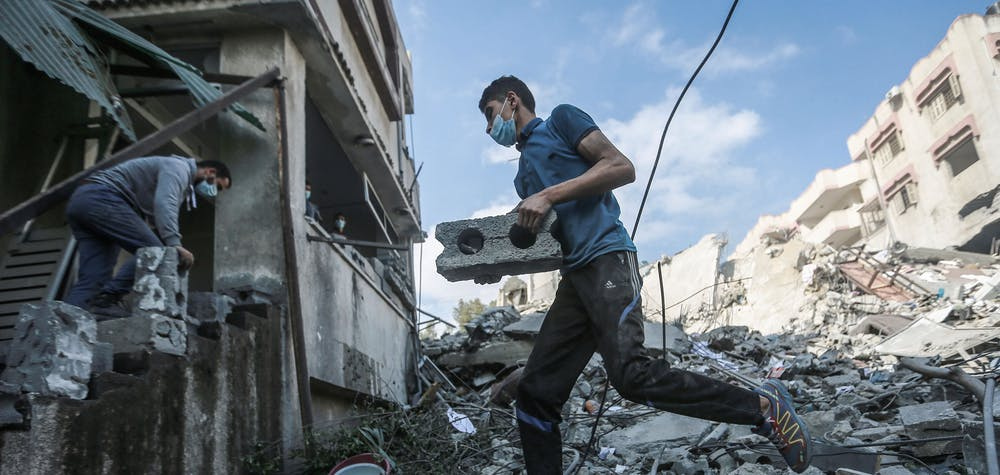 A Palestinian inspects the remains of a destroyed residential building, after it was hit by Israeli airstrikes, amid the escalating flare-up of Israeli-Palestinian violence. Mohammed Talatene/dpa