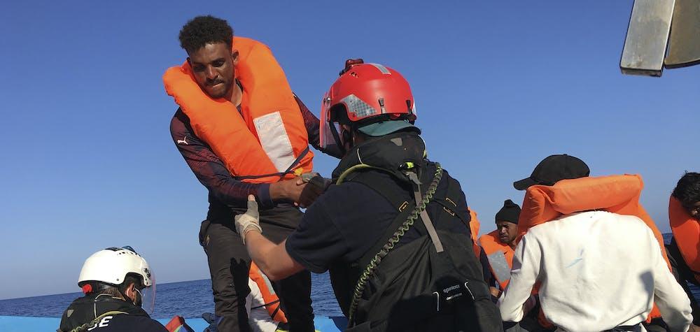 L'un des 47 migrants secourus plus tôt aujourd'hui par des membres de l'ONG française SOS Méditerranée Ocean Viking à 55 km au large des côtes de l'île italienne de Lampedusa est aidé par des sauveteurs le 30 juin 2020. Quarante-sept migrants sur un bateau en bois ont été secourus le 30 juin , 2020 par des militants de l'Ocean Viking, affrétés par le groupe d'aide français SOS-Méditerranée, a déclaré un journaliste de l'AFP à bord.