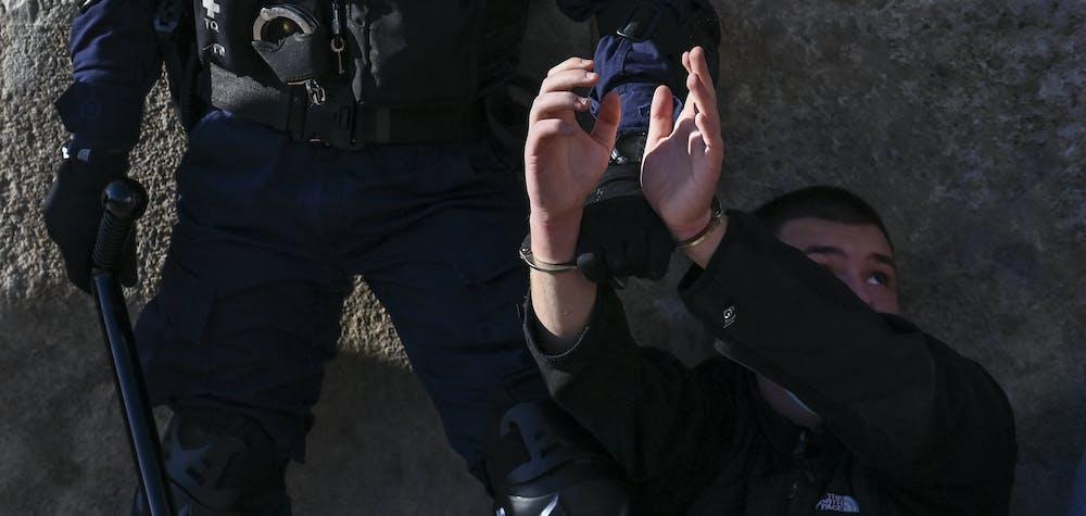 Des agents de la police anti-émeute retiennent un manifestant lors d'une manifestation d'étudiants universitaires contre les législateurs qui s'apprêtent à approuver un plan créant une force de police spéciale pour lutter contre la violence endémique dans les universités, à Athènes le 10 février 2021. Quelque 5 000 étudiants se sont rassemblés à Athènes, selon une source policière, malgré l'interdiction récente des manifestations de plus de 100 personnes pour endiguer la propagation de la pandémie de coronavirus.
