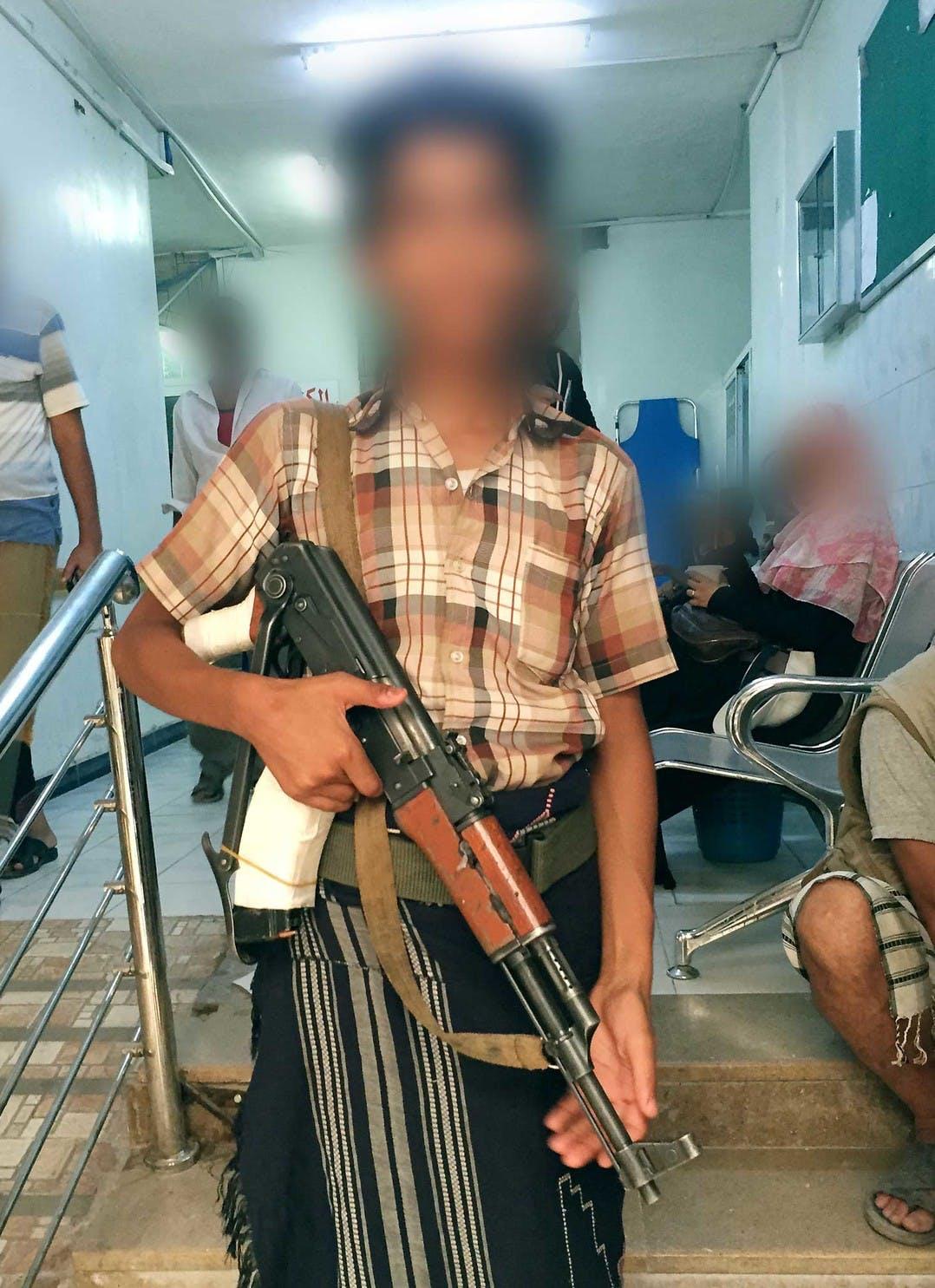 Enfant (âgé de 14-15 ans) portant un fusil d'assaut à l'hôpital al-Rawdha, mai 2015