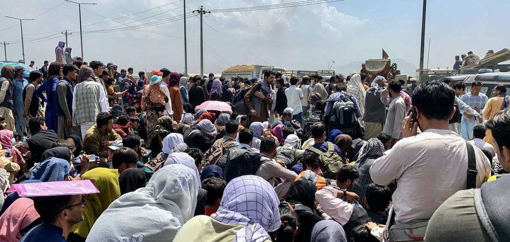 Afghan people gather along a road as they wait to board a U S military aircraft to leave the country, at a military airport in Kabul on August 20, 2021 days after Taliban's military takeover of Afghanistan. (Photo by Wakil KOHSAR / AFP)