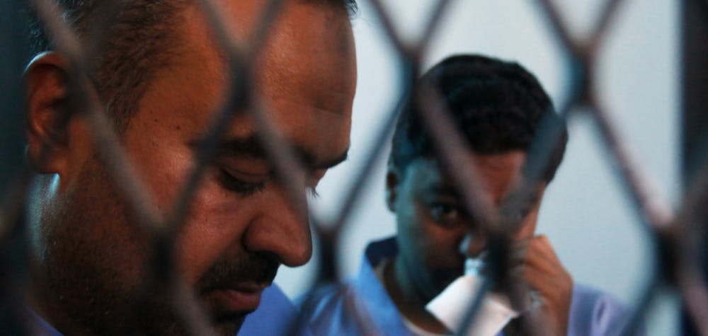 Defendants Abdulkarim Lalji (L) and Hani Ahmad Mohammad, convicted of spying for Iran, stand behind courtroom bars at a state security court of appeals in Sanaa March 25, 2013. The court on Monday commuted their death sentences to five years in prison. The pair were convicted in 2009 of providing the Iranian Embassy in Yemen with military information, according to the Yemen News Agency (SABA).  REUTERS/Khaled Abdullah
