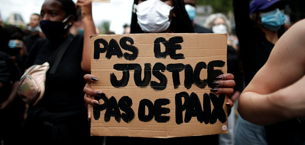 "A demonstrator holds a placard reading ""No justice no peace"" during a protest against police brutality and the death in Minneapolis police custody of George Floyd, at the Place de la Republique square in Paris, France June 13, 2020. REUTERS/Benoit Tessier"