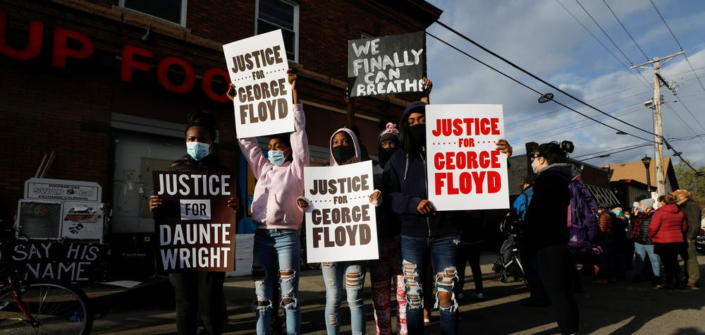 Children hold signs while people react after the verdict in the trial of former Minneapolis police officer Derek Chauvin, found guilty of the death of George Floyd, at George Floyd Square in Minneapolis, Minnesota, U.S., April 20, 2021. REUTERS/Octavio Jones
