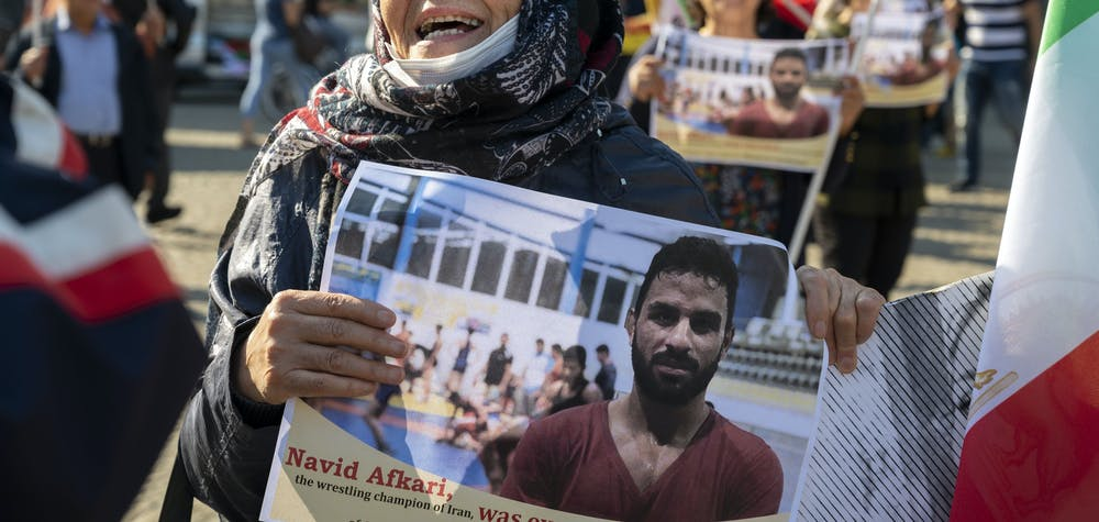 A woman holds a portrait of Iranian wrestler Navid Afkari during a demonstration on the Dam Square in Amsterdam, the Netherlands, on September 13, 2020, against its execution in the southern Iranian city of Shiraz and against the Iranian government. Iran said it executed wrestler Navid Afkari, 27, on September 12, 2020 at a prison in the southern city of Shiraz over the murder of a public sector worker during anti-government protests in August 2018. Reports published abroad say Afkari was condemned on the basis of confessions