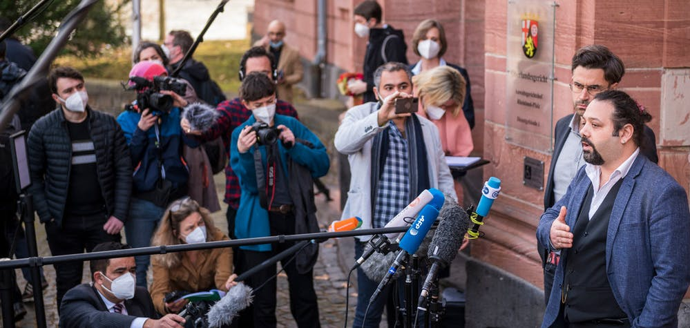 L'avocat Patrick Kroker (2eR) et le co-plaignant Wassim Mukdad (R) s'entretiennent avec les médias devant la cour après le verdict du procès d'un accusé syrien accusé de crimes contre l'humanité dans le premier procès de ce type à émerger du conflit syrien, le 24 février 2021 à Coblence, en Allemagne occidentale. - Eyad al-Gharib, 44 ans, ancien agent des services de renseignement syriens, a été condamné à quatre ans et demi de prison pour complicité de crimes contre l'humanité dans le cadre du premier procès pour torture parrainé par l'État syrien.