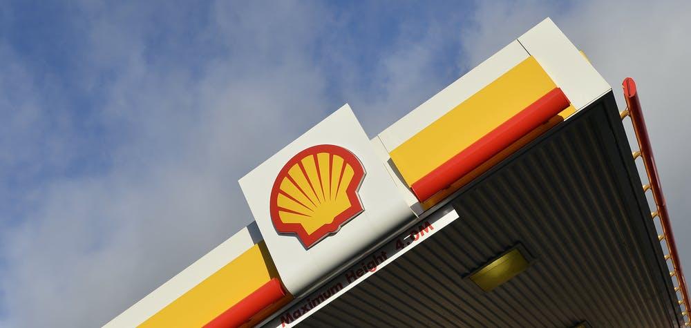 Shell branding is seen at a petrol station in west London, January 29, 2015. Royal Dutch Shell blamed writedowns and forex losses for making almost no money in oil production, its most powerful division, in the last quarter of 2014, causing the company to miss profit forecasts by more than 20 percent. Shell, the largest of the European energy majors, also announced a relatively modest three-year, $15 billion cut in spending to help it weather the plunge in oil prices. REUTERS/Toby Melville (BRITAIN - Tags: BUSINESS ENERGY LOGO)