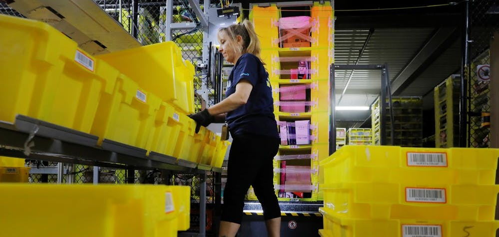 An Amazon employee works to stow items inside of shelves delivered by robots inside of an Amazon fulfillment center on Cyber Monday in Robbinsville, New Jersey, U.S., December 2, 2019.  REUTERS/Lucas Jackson