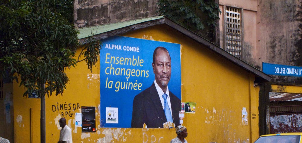 Pedestrians walk past a poster for Guinea presidential candidate Alpha Conde in Conakry, September 13, 2010. Police deployed extra forces around Guinea's capital Conakry on Monday after street fighting between supporters of rivals for its presidential election left one dead and 50 injured over the weekend. REUTERS/Joseph Penney (GUINEA - Tags: POLITICS ELECTIONS)