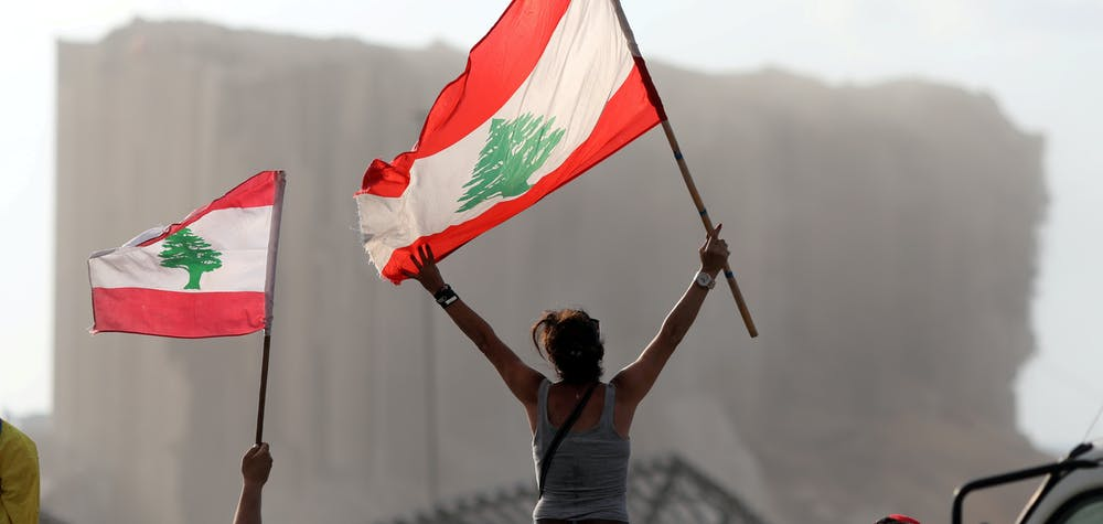 Demonstrators wave Lebanese flags during protests near the site of a blast at Beirut's port area, Lebanon August 11, 2020.