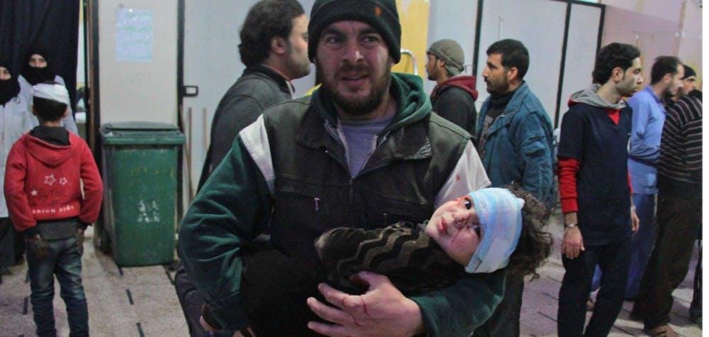 Un père conduit son fils vers un hôpital de fortune après un bombardement sur la ville de Douma  ©  HAMZA AL-AJWEH/AFP/Getty Images