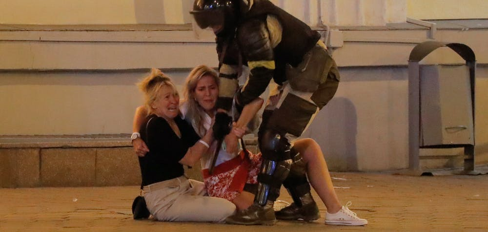 A Belarusian law enforcement officer approaches women, who react while sitting on the pavement during a rally of opposition supporters following the presidential election in Minsk, Belarus August 10, 2020. The opposition rejected official election results handing President Alexander Lukashenko a landslide re-election victory.