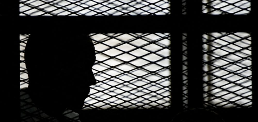Al-Jazeera channel's Australian journalist Peter Greste stands inside the defendants cage during his trial for allegedly supporting the Muslim Brotherhood on June 1, 2014 at the police institute near Cairo's Tora prison. The high-profile case that sparked a global outcry over muzzling of the press is seen as a test of the military-installed government's tolerance of independent media, with activists fearing a return to autocracy three years after the Arab Spring uprising that toppled Hosni Mubarak. AFP PHOTO / KHALED DESOUKI (Photo credit should read KHALED DESOUKI/AFP via Getty Images)