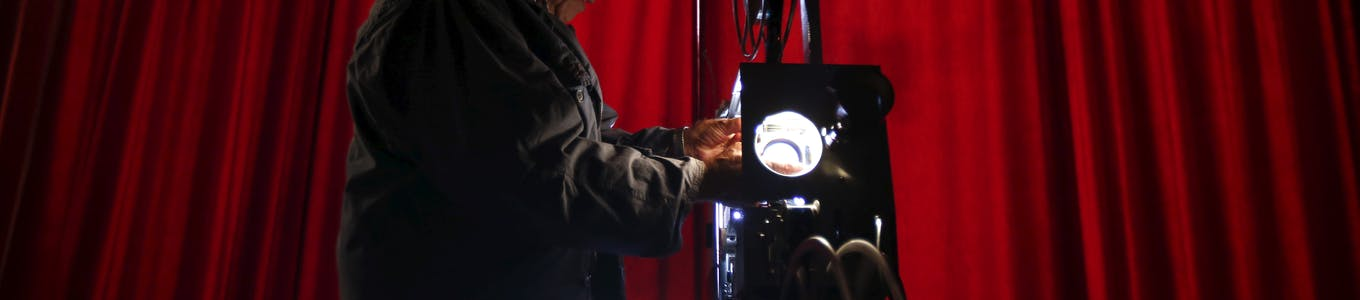 """Projectionist Antonio Feliciano, 75, checks his projector before showing a film in Monforte, Portugal May 16, 2015.  Shades of Oscar-winning classic """"Cinema Paradiso"""" run through the life of Feliciano, a sprightly 75-year-old who fears he may be the last of Portugal's travelling film projectionists.After six decades travelling four million km (2.5 million miles) to screen 4,000 films in Portugal's far-flung villages, Feliciano does not plan to retire just yet. But he is resigned to the fact that the Internet, digital TV and distribution monopolies have made his craft obsolete. Picture taken May 16, 2015. REUTERS/Rafael Marchante"""