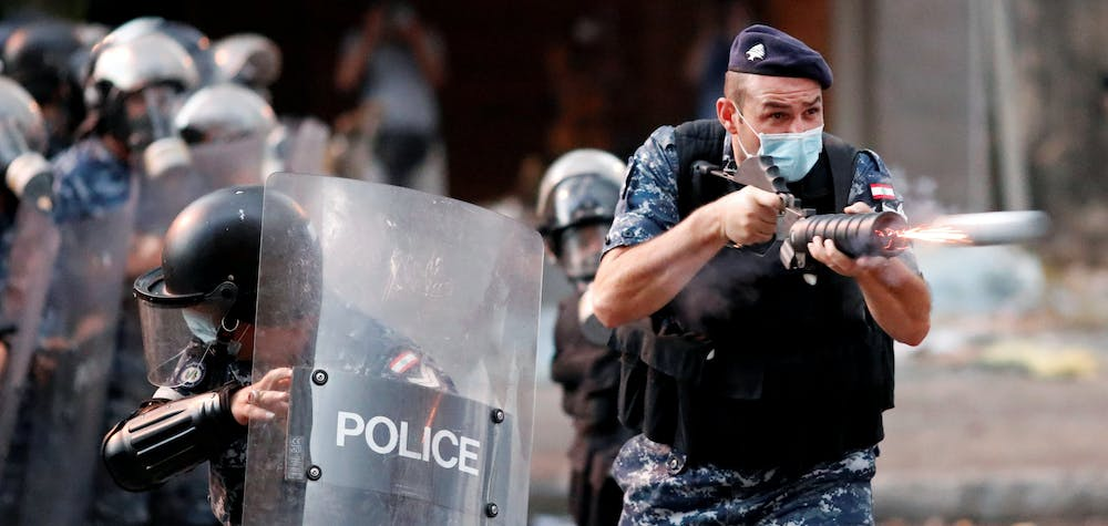 A member of Lebanese riot police fires a weapon during anti-government protests that have been ignited by a massive explosion in Beirut, Lebanon August 10, 2020.