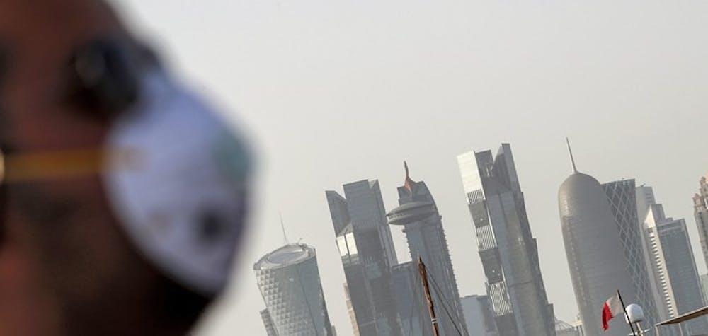 Un homme portant un masque, précaution contre la maladie à coronavirus COVID-19, se promène le long de la corniche de Doha dans la capitale du Qatar le 16 mars 2020. - Les six États membres du Conseil de coopération du Golfe - Bahreïn, Koweït, Oman, Qatar, Arabie saoudite Arabie et Emirats Arabes Unis - ont pris des mesures sans précédent pour lutter contre la pandémie de coronavirus COVID-19, y compris l'arrêt des vols, la fermeture des frontières, la restriction des voyages et la fermeture de toutes les installations de divertissement.