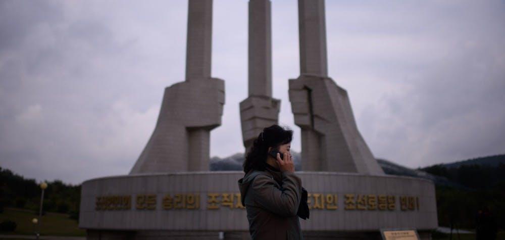 Une femme avec son téléphone portable devant le monument du Parti à Pyongyang 2015