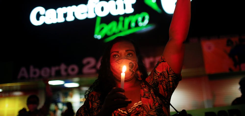 A woman holds a candle during a protest in front of a Carrefour supermarket in Brasilia, Brazil, after Joao Alberto Silveira Freitas was beaten to death by security guards at a Carrefour supermarket in Porto Alegre, November 26, 2020.