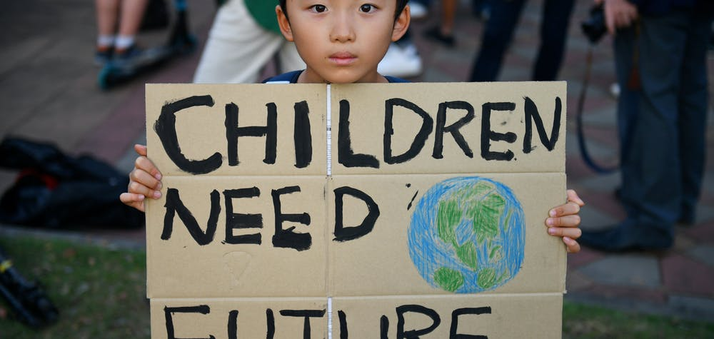 A child holds a placard during a 'drop dead' flashmob protest against climate change consequences at Lumpini Park in Bangkok, Thailand November 29, 2019. REUTERS/Chalinee Thirasupa