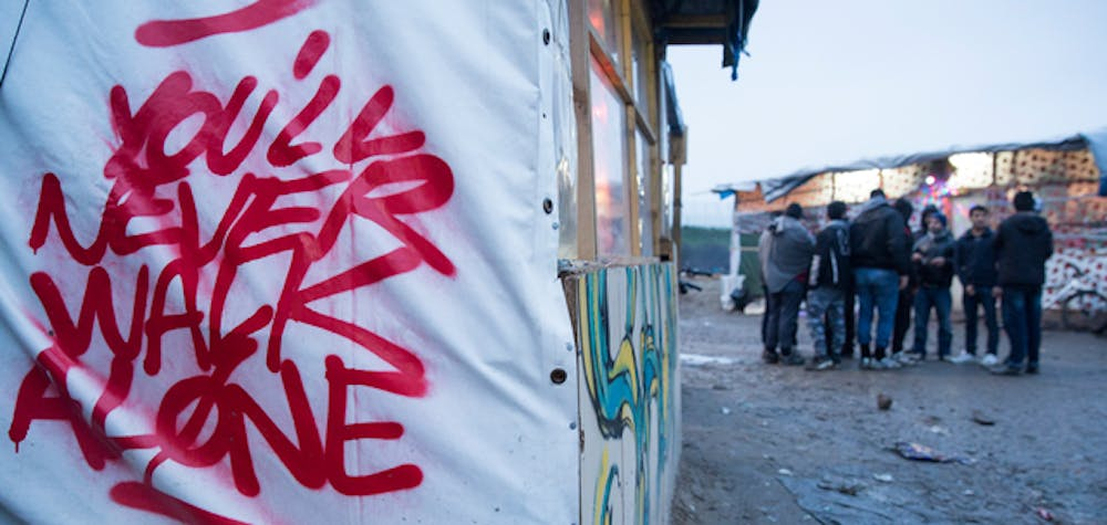 Graffiti is seen close to the entrance of the informal camp in Calais known as 'The Jungle', 23 January, 2016. An estimated 6000 refugees and migrants live in the informal camp situated to the South West of Calais.