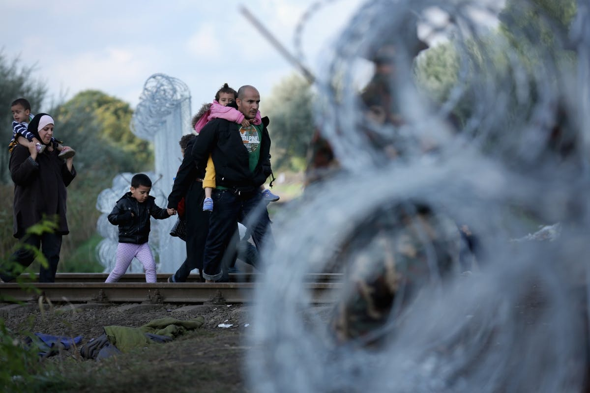 Hungary - Migrants walk through razor wire fencing