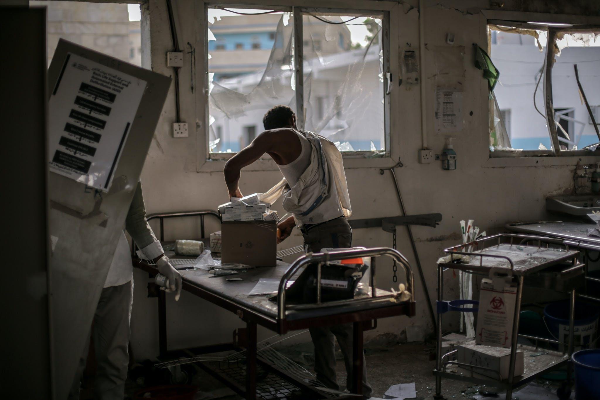 Des employés tentent de sauver du matériel dans l'hôpital de MSF bombardé à Abs, Yemen