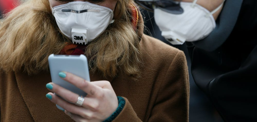 People wearing protective face masks use a smartphone on a street amid coronavirus (COVID-19) concerns in Kiev, Ukraine March 17, 2020.