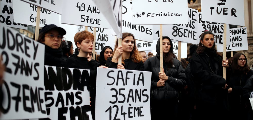Women hold up signs during a demonstration to protest femicide and violence against women in Paris, France, November 23, 2019. REUTERS/Christian Hartmann