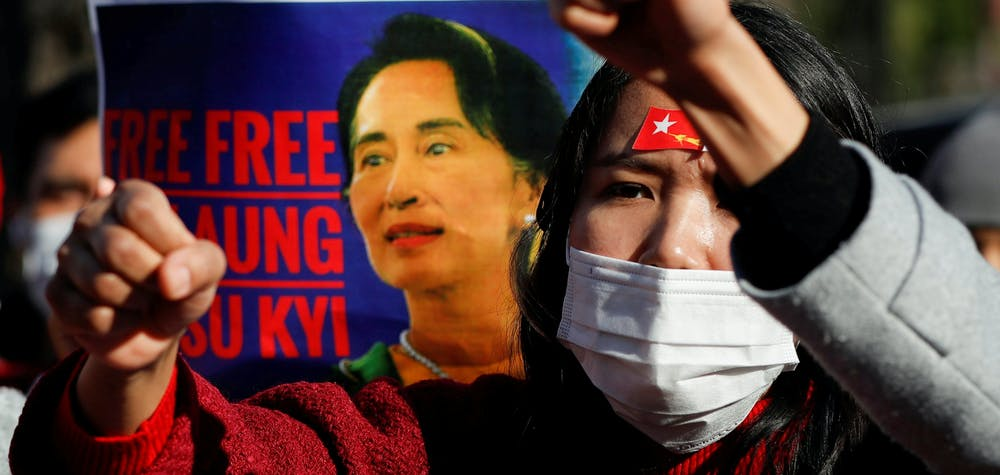 FILE PHOTO: Protesters from Myanmar residing in Japan raise their fists and hold a poster depicting Aung San Suu Kyi during a rally against Myanmar's military, after it seized power from a democratically elected civilian government and arrested Suu Kyi, outside Foreign Ministry in Tokyo, Japan February 3, 2021. REUTERS/Issei Kato/File Photo