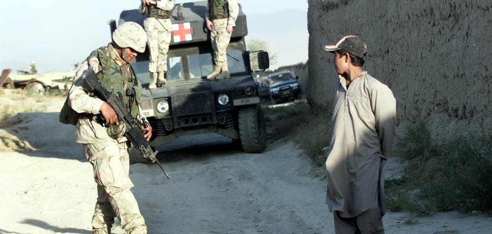 An Afghan boy watches U.S. soldiers at a check point near the site of a blast outside the U.S. headquarters at Bagram north of Kabul on October 3, 2003. At least four Afghans were killed and two were missing after the blast outside the main base of U.S. forces in Afghanistan, which a U.S. officer said may have been caused by children playing with bombs.